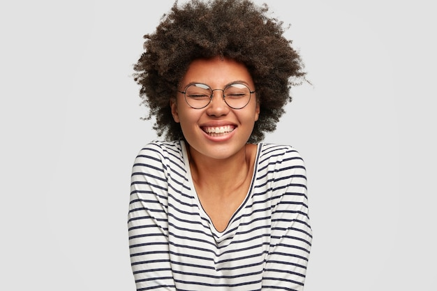 Headshot of beautiful smiling funny dark skinned female has afro haircut, laughs at something, keeps eyes closed from pleasure, dressed in striped sweater, isolated over white wall. happiness