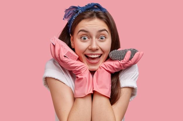 Primo piano del volto della bella signora sorridente tiene due spugne, felice di finire con le faccende domestiche, indossa guanti di gomma e maglietta bianca
