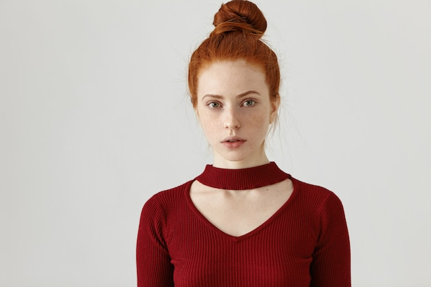 Headshot of beautiful young female with freckles and ginger hair knot standing at white wall