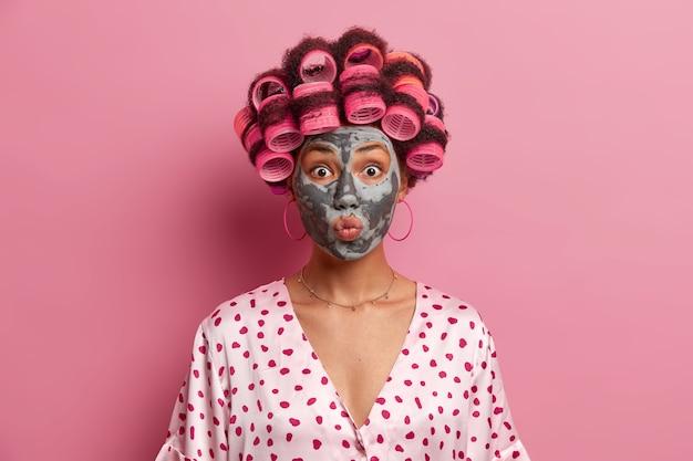 Il primo piano del volto di bella giovane donna mantiene le labbra arrotondate, applica una maschera di bellezza, indossa i bigodini, vestita con una veste di seta casual, isolata sopra il rosa. routine di bellezza e concetto di acconciatura