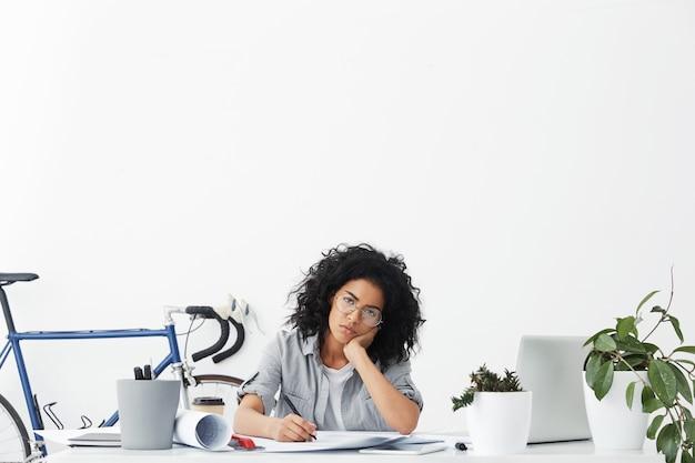 Headshot of bored african female student doing homework, preparing for exams