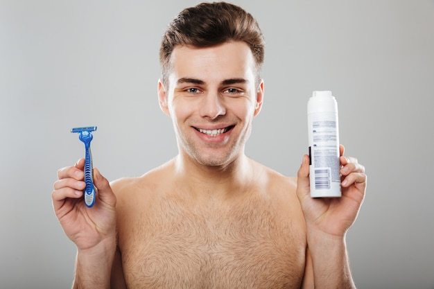 Headshot of brunette happy guy 30s being undressed at bathroom holding razor and shaving cream over grey wall