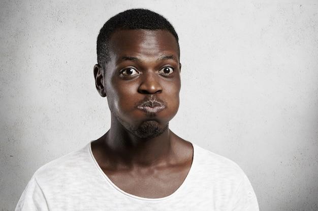 Primo piano del volto di un giovane africano con gli occhi da insetto che fa smorfie, gonfiando le guance, trattenendo il respiro, sforzandosi di non ridere con l'espressione del viso buffo, facendo clown e divertendosi al chiuso
