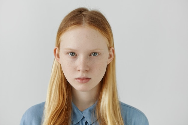 Headshot of caucasian girl with freckles, blond hair and light eyes dressed in blue school shirt standing against white wall