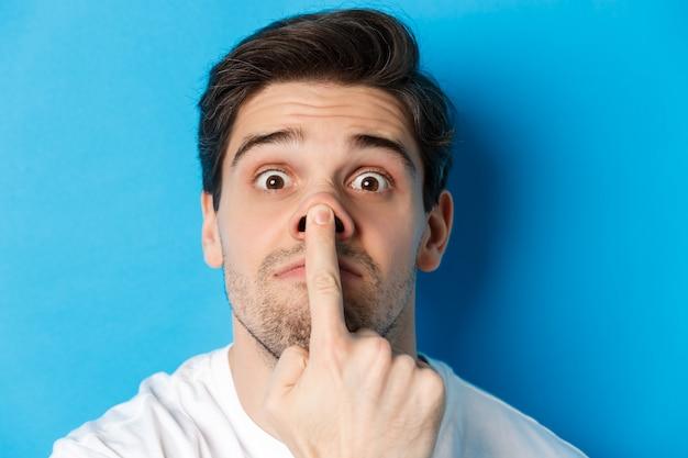 Colpo in testa di un ragazzo caucasico che fa espressioni divertenti, in piedi su sfondo blu