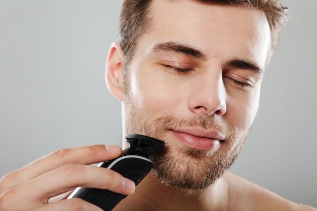 Headshot of caucasian pleased guy 30s being undressed at bathroom while shaving face with trimmer over grey wall