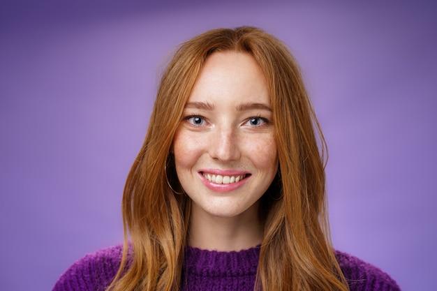 Colpo in testa di affascinante giovane donna rossa attraente e felice con lentiggini e sorriso bianco brillante, sorridendo soddisfatto alla telecamera mentre posa su sfondo viola amichevole e felice.