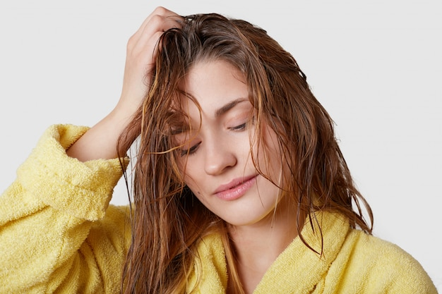 Headshot of charming thoughtful young female adult keeps gaze down, holds hand on head, has wet hair after taking shower