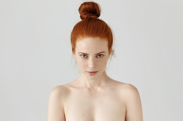 Headshot of charming young lady wearing her ginger hair in knot staring with seductive look, posing topless at blank wall, freckles covering her face and shoulders.