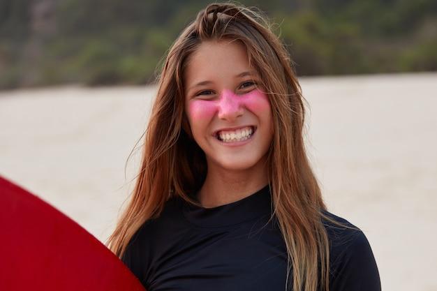 Headshot di allegro giovane turista impara a fare surf, pose contro la riva del mare