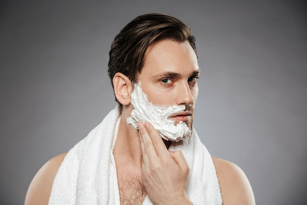 Headshot of concentrated handsome man putting shaving foam on face, while having morning skincare isolated over gray wall
