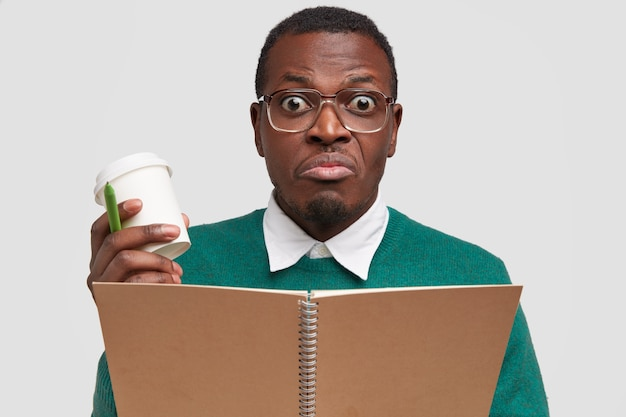 Headshot of confused black male student wonk looks in bewilderment, writes down text information at notebook