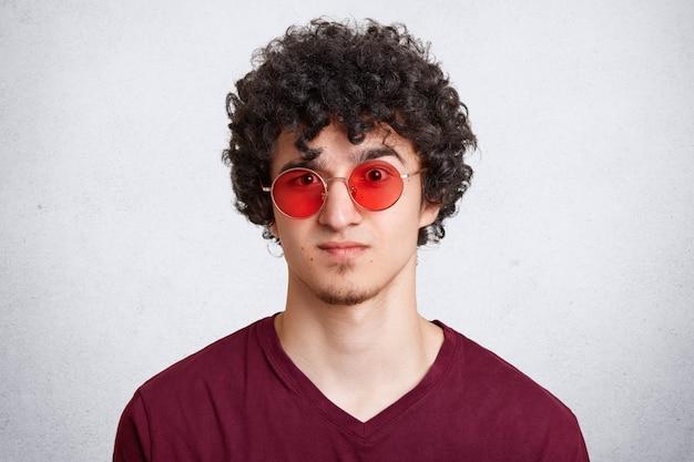 Colpo in testa di giovane maschio barbuto alla moda freddo con capelli ricci