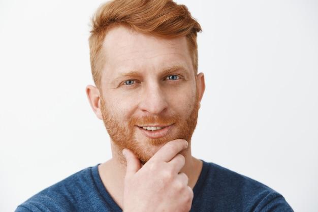 Primo piano del volto di un ragazzo dai capelli rossi attraente, creativo e intrigato con setole, barba che si sfrega e sorride, con un ottimo piano o idea che guarda con curiosità, interessato al muro grigio