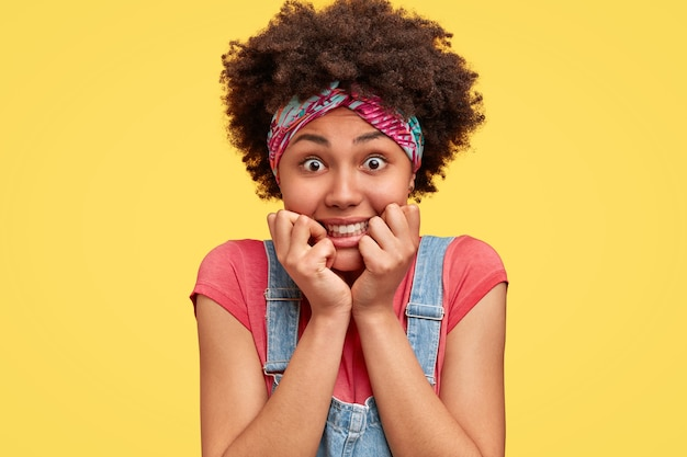 Il colpo alla testa della donna riccia tiene il mento, ha un'espressione positiva, apre gli occhi, un sorriso piacevole, indossa la fascia e la tuta, isolato su un muro giallo. affascinante giovane donna afro-americana.