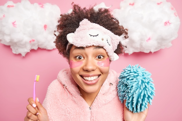 Headshot of curly haired young woman with positive expression holds toothbrush and bath sponge dressed in pajama isolated over pink wall white clouds. people oral hygiene beauty concept
