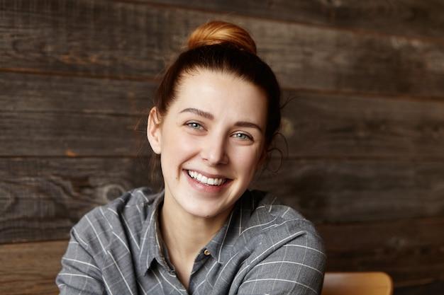 Primo piano del volto della ragazza carina con i capelli bun trascorrere la pausa pranzo al ristorante con pareti in legno