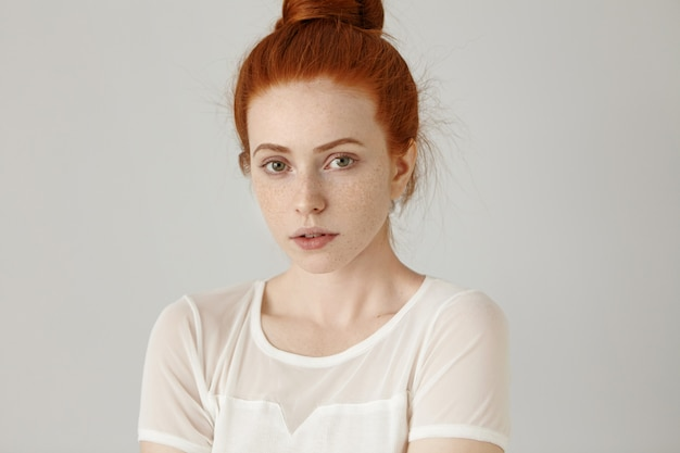 Headshot of cute girl with pleasant features posing at grey wall. attractive young caucasian woman with ginger hair in bun and freckles looking and smiling with her lips slightly parted