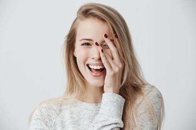 Headshot of cute woman with dark eyes, blonde long hair, happy gentle smile rejoicing her success.