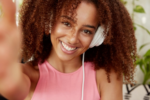 Headshot of cute young woman with frizzy hair, makes selfie while listens music in headphone, going to share photo in social networks. pretty african american female meloman makes photo of herself
