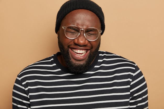Primo piano del volto dell'uomo barbuto dalla pelle scura che ride felice, socchiude gli occhi dalla gioia, mostra i denti bianchi, indossa un cappello nero e un maglione a righe, isolato su uno spazio marrone