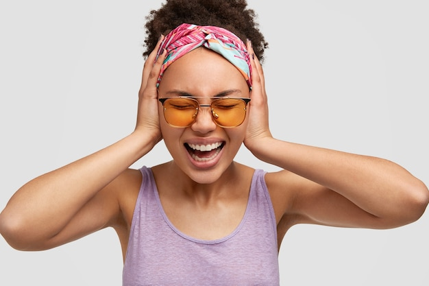 Headshot of depressed beautiful african american female yells with irritation, keeps hands on ears, doesn`t want to hear awful news, can`t believe in something terrible, isolated over white wall