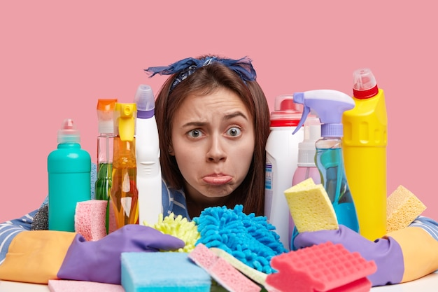 Colpo di testa di malcontento giovane donna porta il labbro inferiore con insoddisfazione, ha molto lavoro, abbraccia molti detergenti chimici e spugne