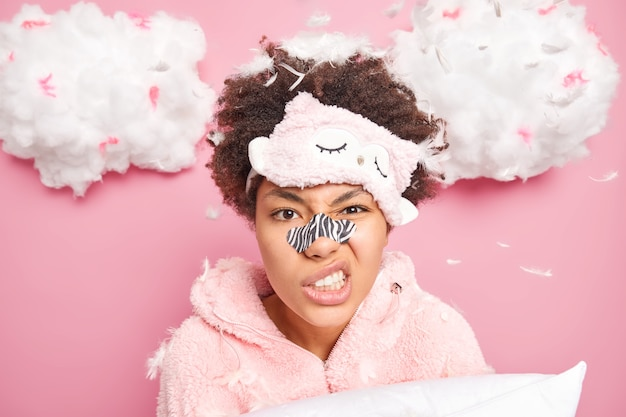 Headshot of displeased curly haired woman smirks face clenches teeth applies nose patch to reduce wrinkles wears blindfold and nightwear isolated over pink wall