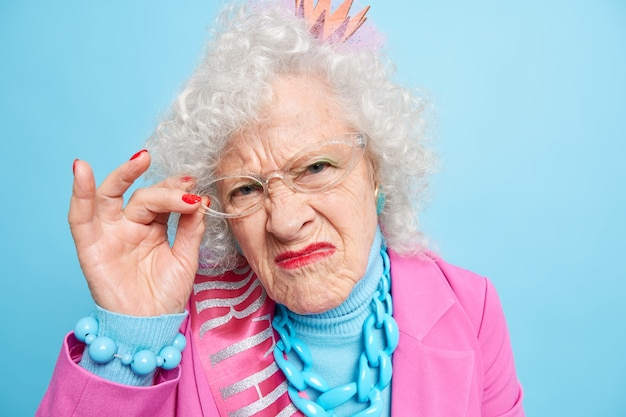 Headshot of displeased grey haired mature woman looks with grumpy expression, keeps hand on spectacles squints face from displeasure poses well dressed indoor