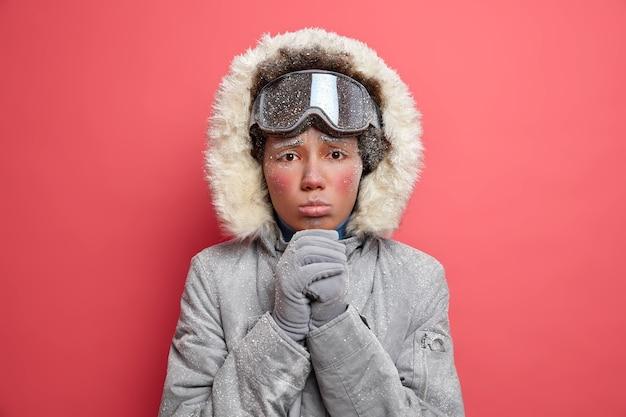 Headshot di donna scontenta con la faccia fredda tiene le mani unite sguardi con espressione implorante, indossa una calda giacca invernale