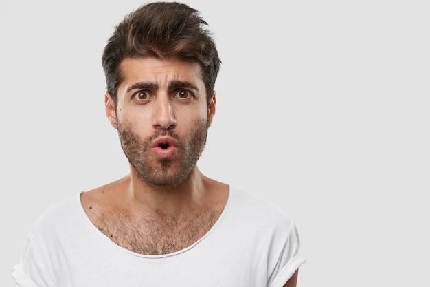 Primo piano del volto di un bell'uomo con la barba lunga emotivo ha un taglio di capelli alla moda, le labbra arrotondate e guarda con stupore