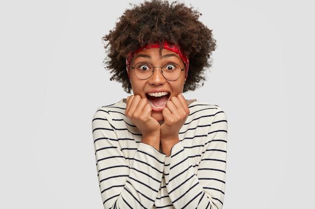 Headshot di giovane donna nera sbalordita emotiva apre la bocca con stupore