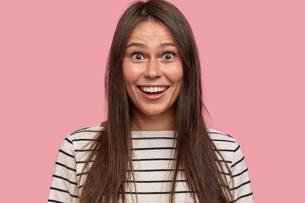 Headshot di donna europea bruna eccitata con espressione positiva sorpresa