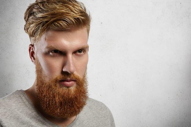 Primo piano del volto di uomo alla moda giovane hipster con barba folta e taglio di capelli alla moda che esamina la distanza con un'espressione seria e fiduciosa sul viso.
