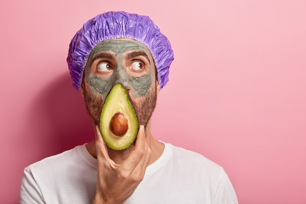 Headshot of focused man looks up, keeps slice of avocado near face, applies clay mask, removes black dots on skin