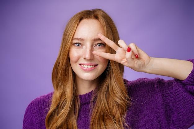 Colpo in testa di studentessa rossa felice amichevole e ottimista in maglione viola che mostra vittoria o gesto di pace sopra l'occhio come mossa di ballo della discoteca che sorride ampiamente sopra fondo viola.