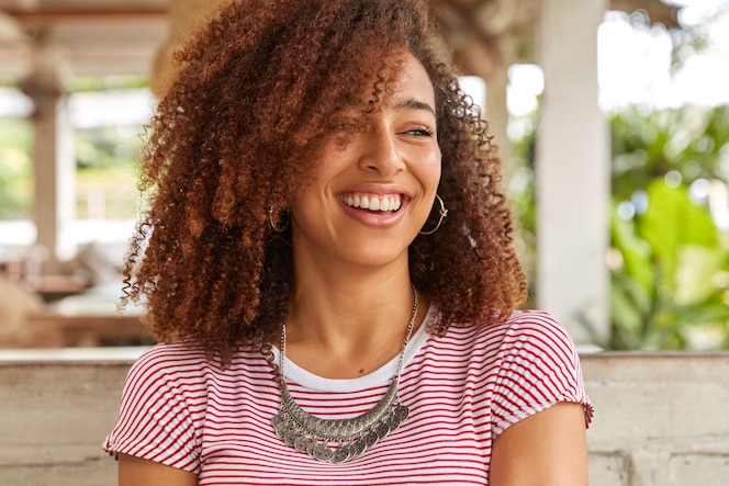 Headshot of funny black woman with curly hair, laughs at good joke, has toothy smile, shows white perfect teeth, wears striped casual t shirt, poses at terrace cafeteria