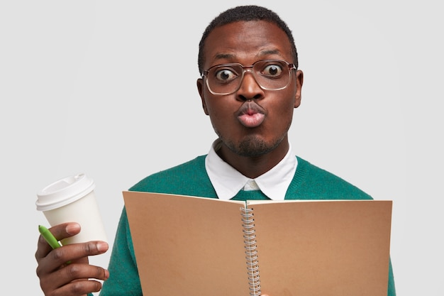 Headshot of funny male student pouts lips, makes grimace, wears big optical glasses, formal white shirt under sweater, holds takeaway coffee