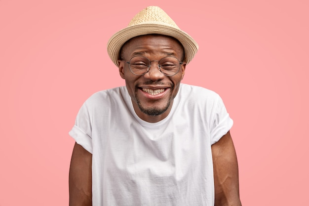 Headshot of funny positive cheerful dark skinned man giggles happily, has comic facial expression