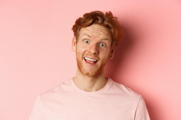 Colpo alla testa di un ragazzo dai capelli rossi divertente che mostra la lingua, facendo facce stupide alla telecamera, in piedi gioioso su sfondo rosa. copia spazio
