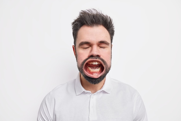 Headshot of furious mad bearded man stands with eyes shut keeps mouth opened screams loudly expresses anger dressed in casual shirt