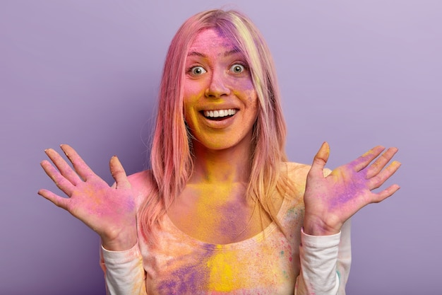 Headshot of glad female with toothy smile, happy reaction, spreads hands, dirty with multicolored dry powder, has fun on traditional holi festival, isolated against purple wall. vibrant colors