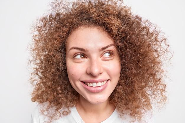 Headshot di bella ragazza riccia allegra guarda lontano in studio contro il muro bianco.
