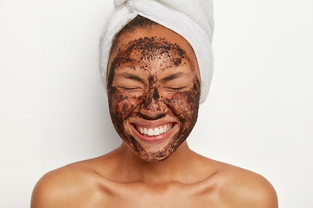 Headshot of good looking overjoyed young woman keeps eyes shut, smiles broadly, shows white perfect teeth, wears wrapped towel on head, peels face with coffee scrub, stands shirtless indoor.