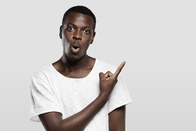 Headshot of good-looking shocked african male dressed in white t-shirt, gesturing in surprise and astohisnment, pointing at blank wall, showing copy space for your text or promotional information