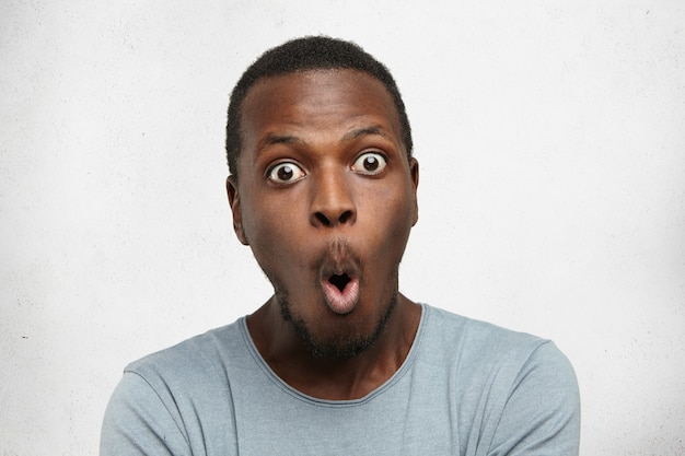 Headshot of goofy surprised bug-eyed young dark-skinned man student