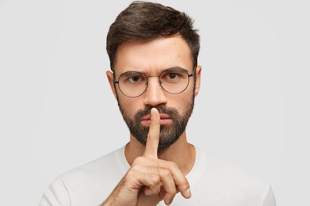 Il primo piano del volto di un bel maschio caucasico barbuto fa un gesto di silenzio, guarda seriamente, ha uno sguardo concentrato, richiede il silenzio completo, posa contro il muro bianco. persone e silenzio