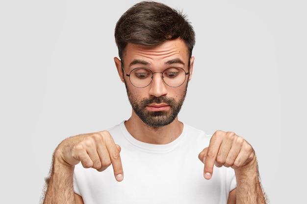 Headshot of handsome bearded male points down with surprised look, notices something on floor, wears glasses, dressed in casual t-shirt, isolated over white wall. people and astonishment