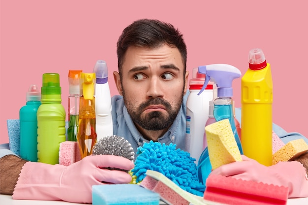 Headshot of handsome bearded man focused aside, has puzzled look, surrounded with cleaning detergents