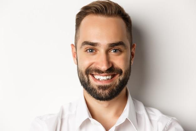 Primo piano del volto dell'uomo barbuto bello sorridente, in piedi su sfondo bianco.